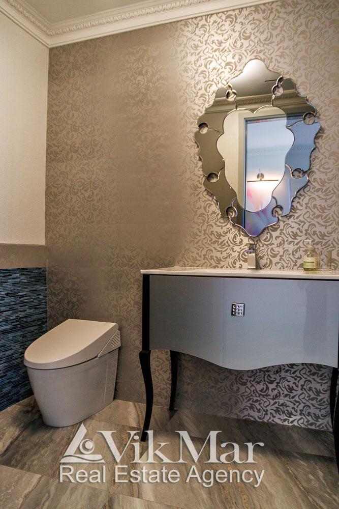 Общий вид элегантного интерьера туалетной комнаты в стиле «Ар-Деко с классическими орнаментальными карнизами