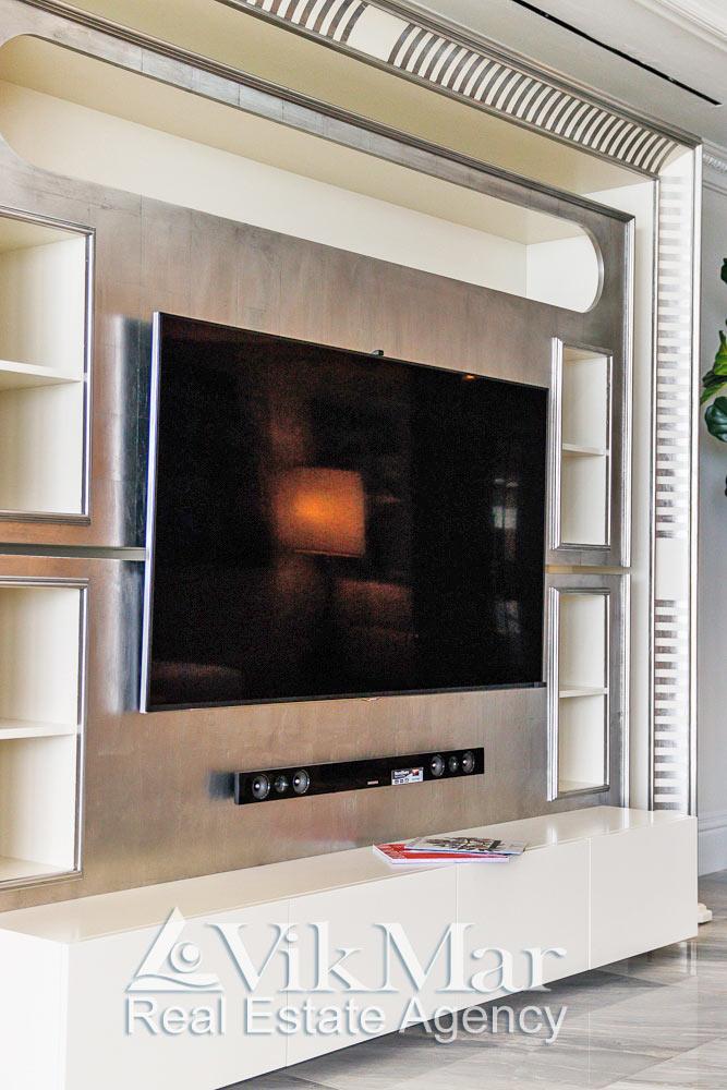 Общий вид декоративного портала и встроенного домашнего кинотеатра салона гостиной элитной квартиры