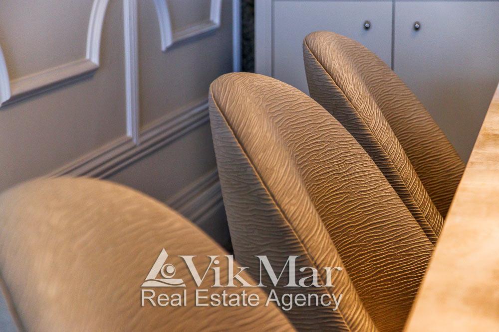 Крупный план декоративной отделки спинок стульев в стиле модерн в составе комплекта гостиной мебели квартиры