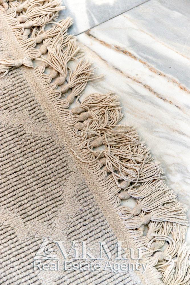 Фото фрагмента декоративного ковра на мраморном покрытии пола в спальном помещении квартиры в комплексе St. Regis Bal Harbour в Майами Бич, США