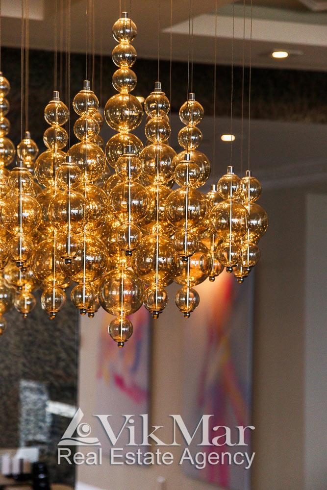 Общий вид комбинированной люстры в обеденной зоне западного салона гостиной элитной квартиры апартаментов