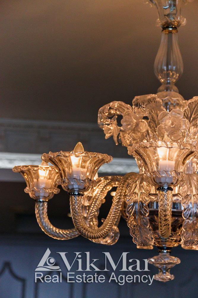 Общий вид роскошной люстры в стиле «Неоклассицизм» в спальне хозяев элитной квартиры апартаментов в Майами Бич