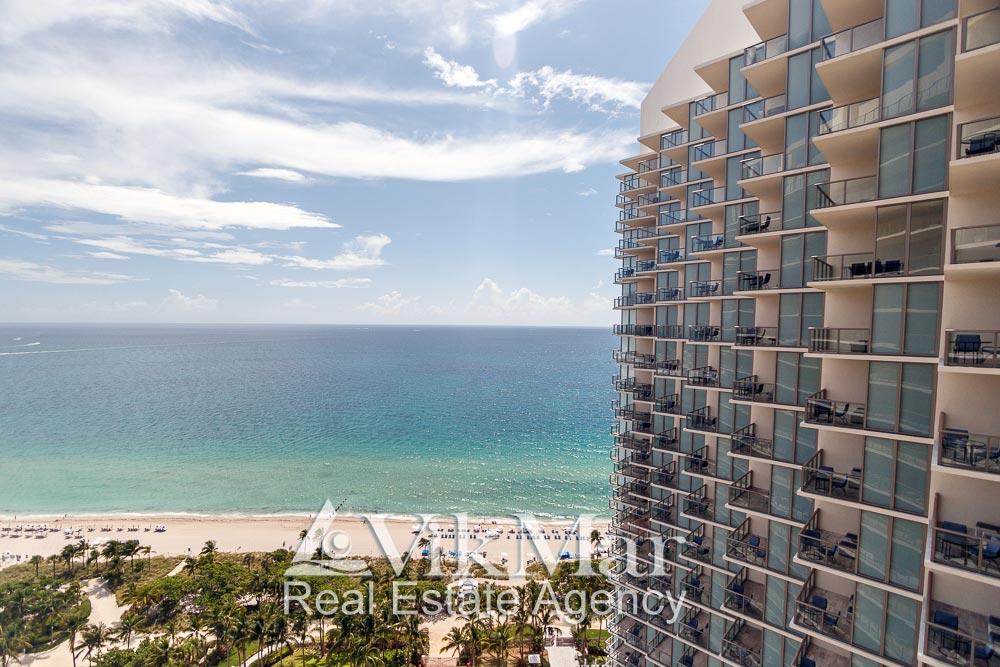 Общий вид на здание «Центральной» башни и курортную зону отдыха на берегу океана из квартиры апартаментов в комплексе «St. Regis»