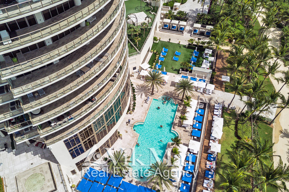 Комфортабельная зона отдыха с открытыми плавательными бассейнами и площадками соляриями у здания «Центральной» башни комплекса «St. Regis Bal Harbour»