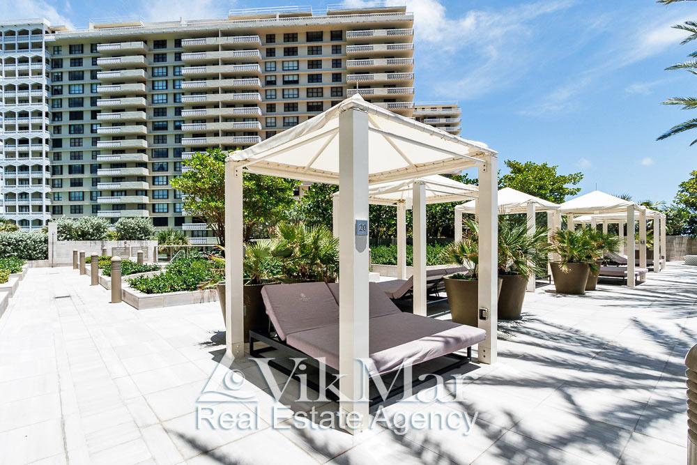 Фото открытого солярия с теневыми навесами в элитном пляжном клубе жилого комплекса «St. Regis Bal Harbour Resort»