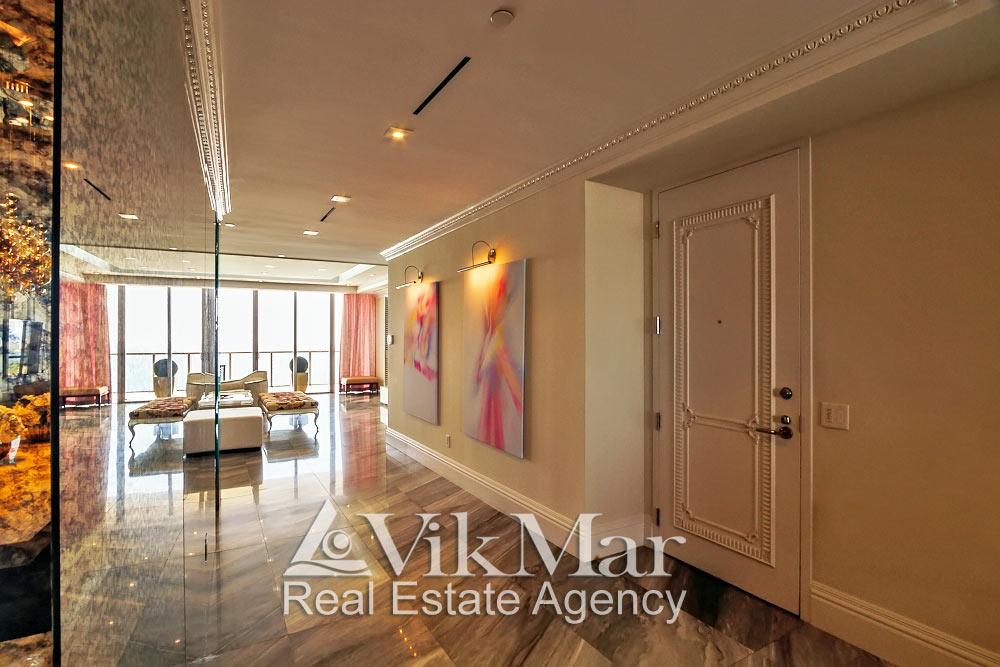 Интерьер прихожей со входом в квартиру со стороны гостиной элитных апартаментов жилого кондоминиума St. Regis Bal Harbour