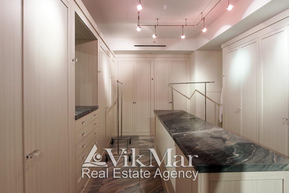 Центральная фото перспектива интерьера гардеробной спальни хозяев элитной квартиры апартаментов в жилом комплексе St. Regis