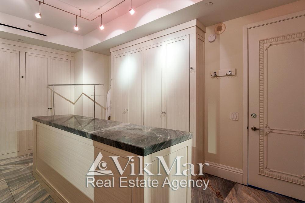 Общий вид элегантной декоративной отделки гардеробной спальни хозяев элитных апартаментов в Майами Бич