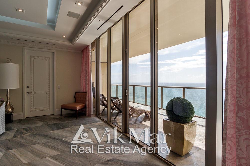 Общий вид восточного балкона со стороны витражного остекления салона гостиной элитной квартиры апартаментов в Майами Бич