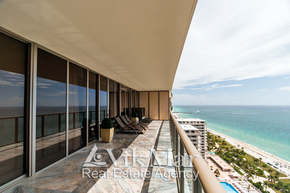 Фото внутренней отделки, меблировки и панорамного вида на океан с восточного балкона галерейного типа элитных апартаментов в жилом комплексе St. Regis Bal Harbour в Майами Бич
