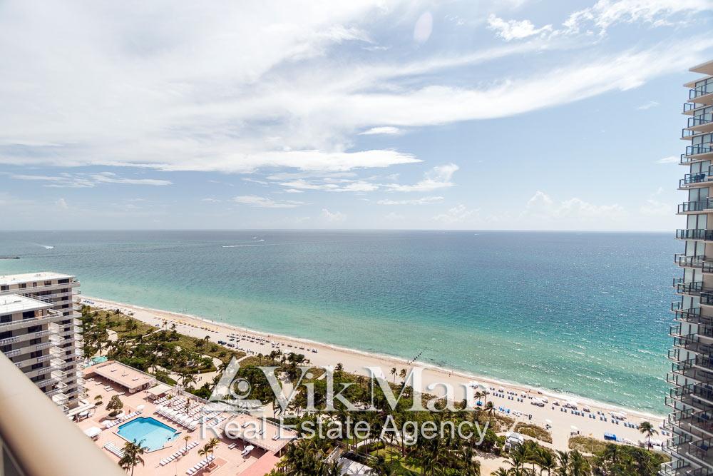 Панорамный вид на пляжную зону отдыха и акваторию Атлантического океана с восточного балкона элитных апартаментов в курортном комплексе St. Regis Bal Harbour, Майами Бич