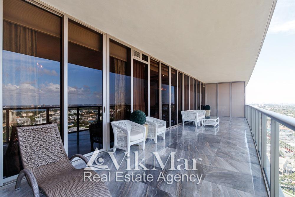 Общий вид пространства, декоративной отделки и меблировки западного балкона элитных апартаментов в жилом комплексе St. Regis Bal Harbour