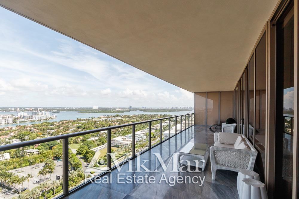 Перспектива отделки и меблировки западного балкона элитной квартиры с видом на район Bal Harbour и залив Бискейн в Майами Бич