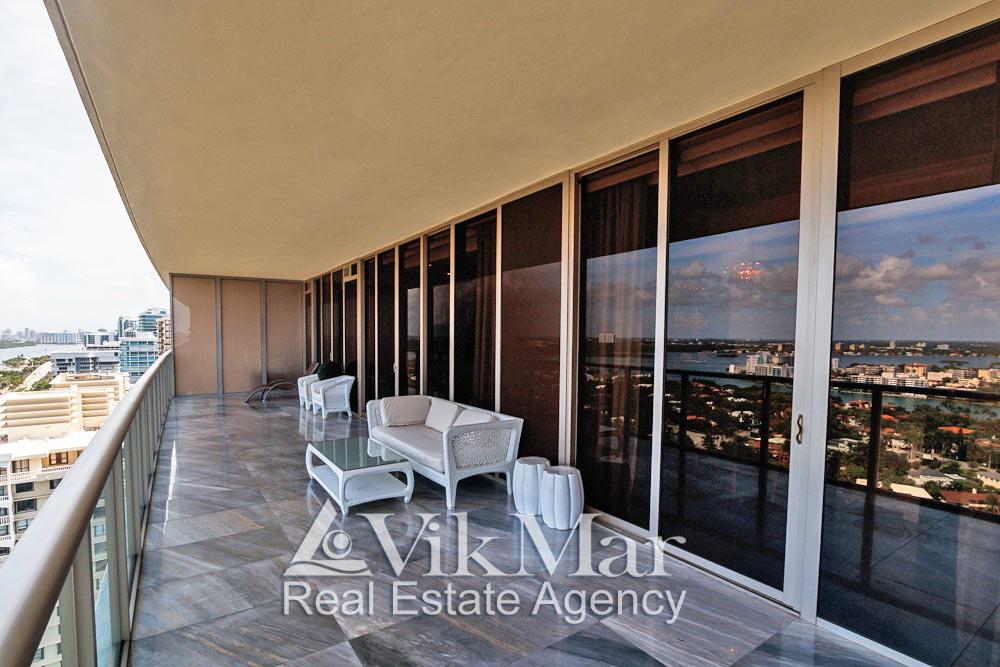 Фото перспектива открытого пространства и меблировки зоны отдыха на западном балконе элитной квартиры в Майами Бич, США