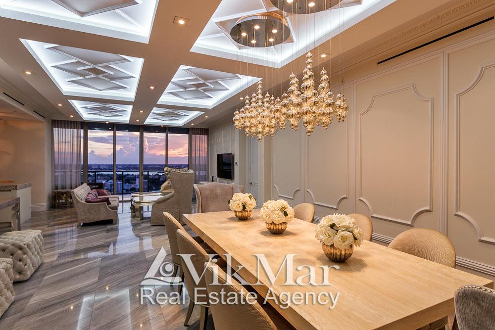 Фото перспектива элегантного интерьера западной гостиной с видом на районы Майами при вечернем декоративном освещении