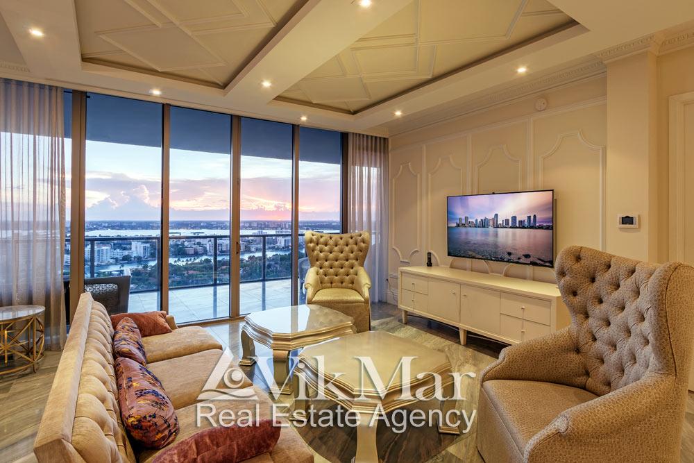 Крупный план стильной меблировки зоны отдыха западного салона гостиной с видом на районы Майами вечером