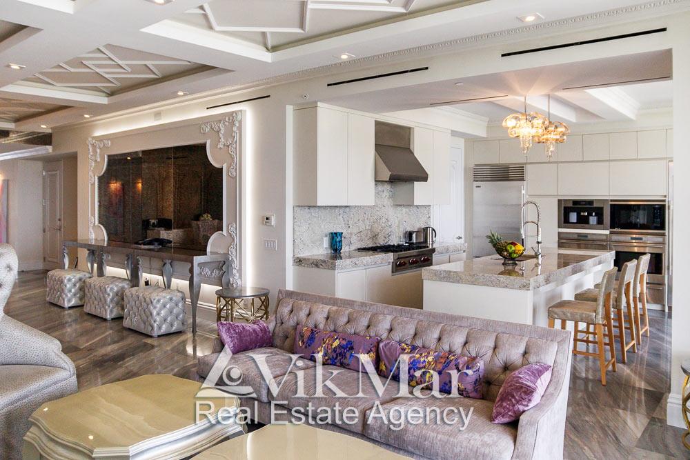 Интерьер кухни столовой на 5 обеденных мест со стороны западной гостиной элитной квартиры апартаментов в Майами Бич, США