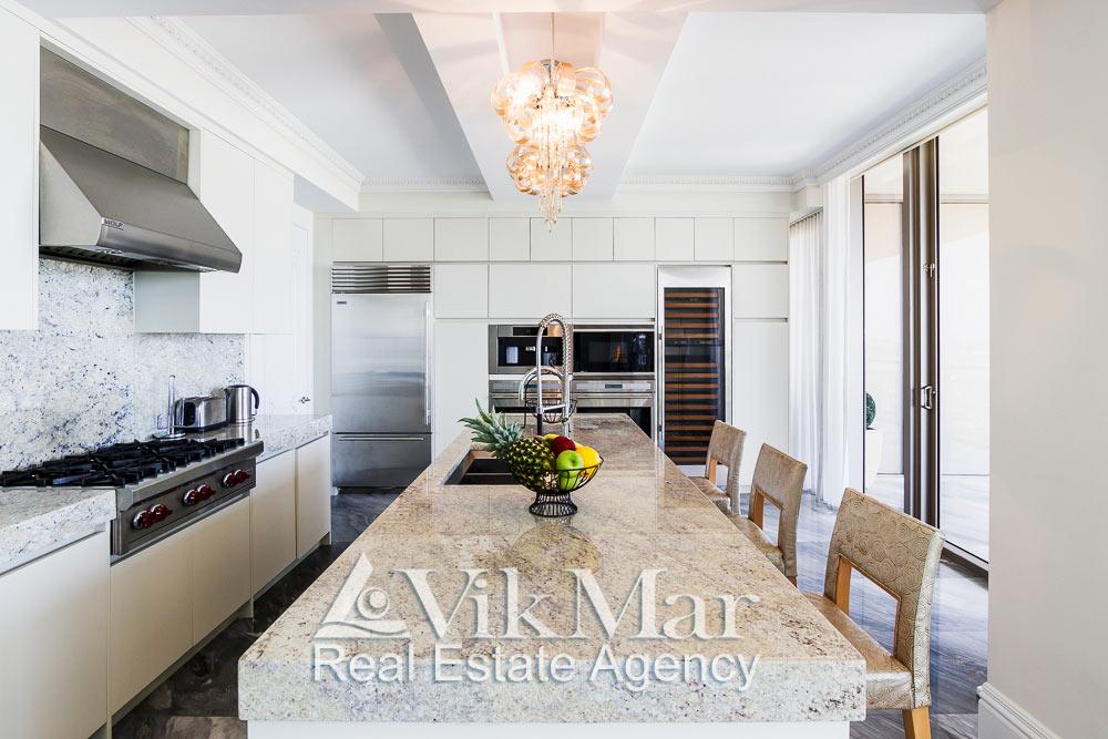 Центральная перспектива интерьера кухни столовой со стороны западной гостиной (Family Room) элитной квартиры апартаментов в Майами Бич, США