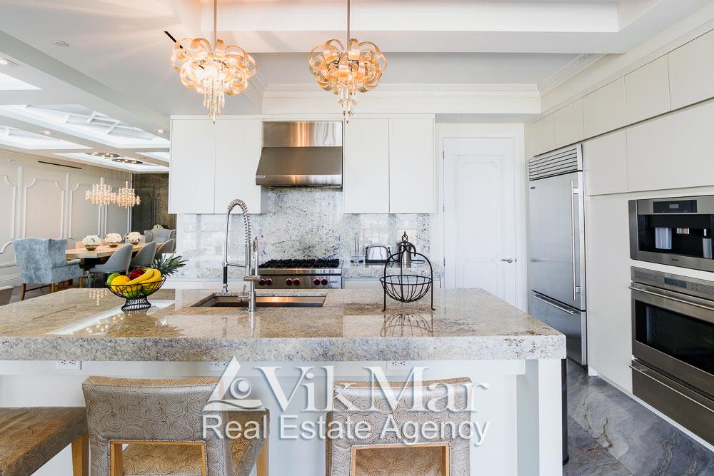 Общий вид обеденной мебели и бытового оборудования в интерьере кухни столовой элитных апартаментов жилого комплекса St. Regis Bal Harbour