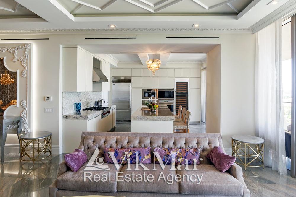 Фронтальная перспектива «свободного» пространства западной гостиной (Family Room) и кухни столовой элитных апартаментов в жилом комплексе St. Regis Bal Harbour в Майами Бич, США