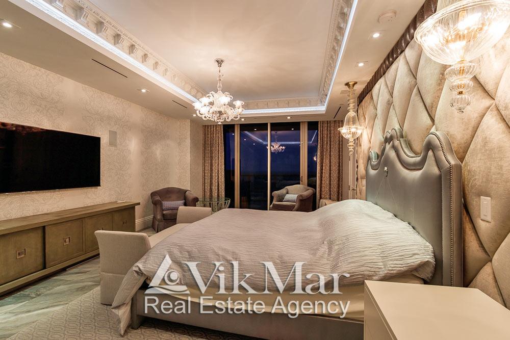 Фото элегантной меблировки и декоративного освещения спальни хозяев элитной квартиры апартаментов в жилом комплексе St. Regis Bal Harbour